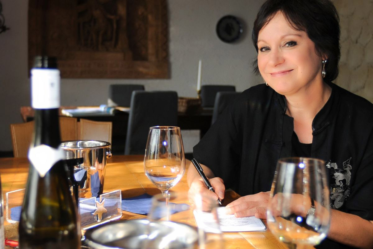 Woman sitting at a wood table, taking notes, empty wine glasses, smiling at camera
