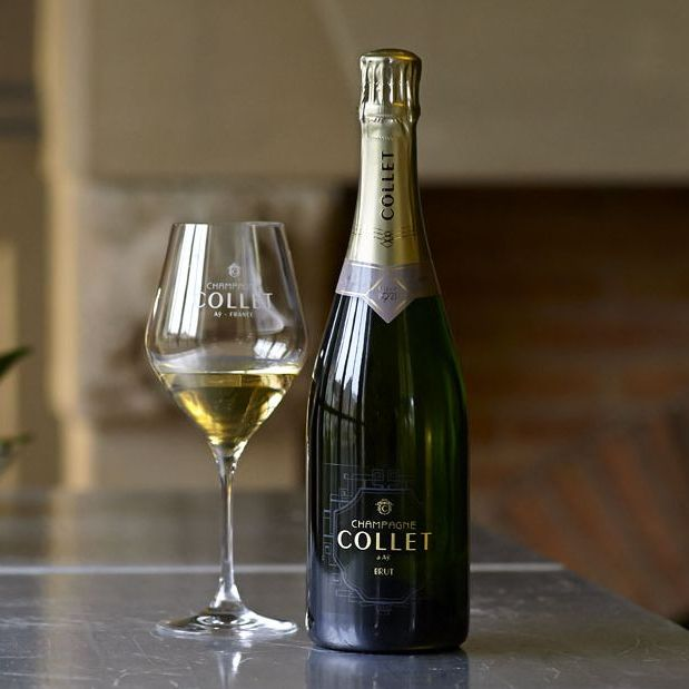 A Champagne Collet-branded white wine glass sits one-third full beside a bottle of Champagne Collet Brut Origin. Both are atop a marble countertop, with a faint view of a stone fireplace in the background.