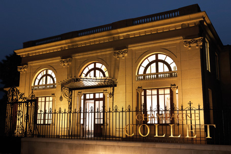 An underlit front view of the Maison Champagne Collet in the nighttime.