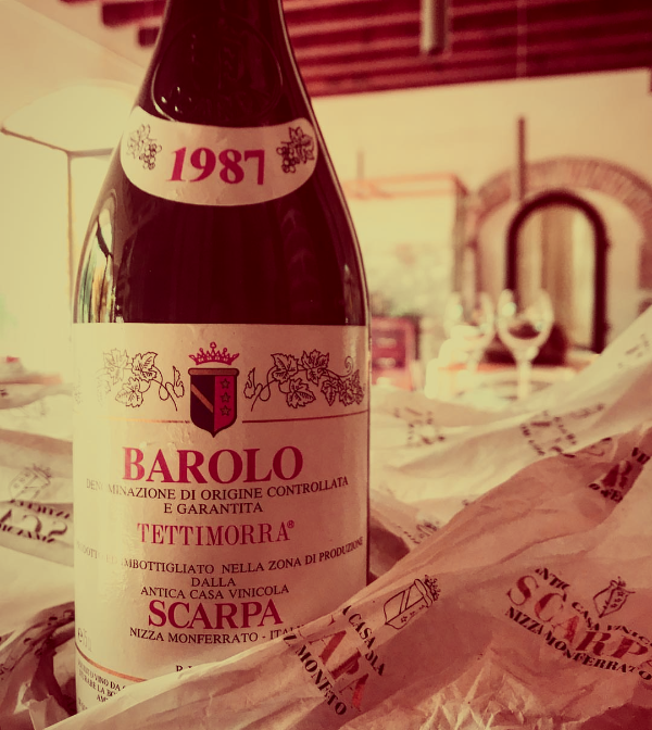 A sepia-toned photo of 1987 Barolo Tettimorra Scarpa, sitting attop its freshly removed wrapping paper, the view of a classic Italian dining room in the distance.