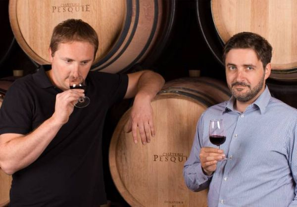 The Bastide Brothers standing in front of several wooden barrells in Chateau Pesquie's cellars. One is sampling the aroma of red wine, while the other holds his glass looking at the camera.