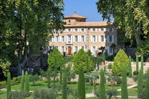 Chateau Pesquie and its courtyard and gardens on a sunny day.