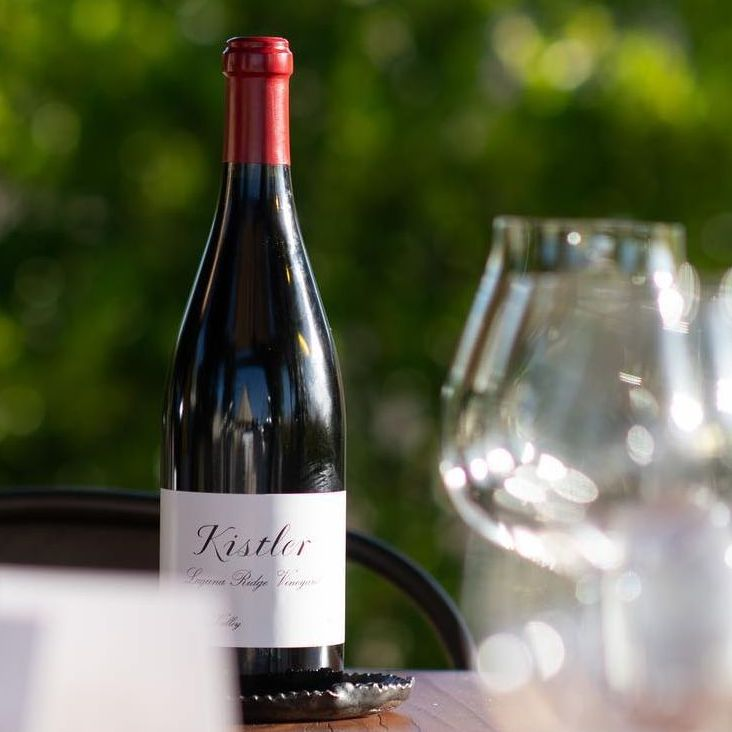 A bottle of Kistler Russian River Pinot Noir sits on an outdoor bistro table, with faded foliage in the distant background, and out-of-focus red wine glasses in the foreground.