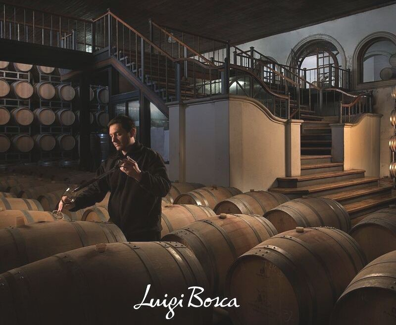 Winemaker in the Bodega Luigi Bosca wine cellar, standing amongst rows of barrels of wine, sampling from a barrel with a dropper into a wine glass.