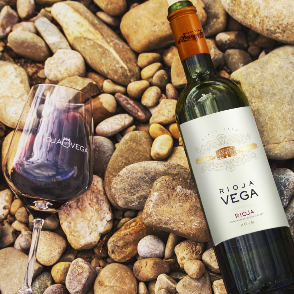 A tasting of Rioja Vega's 2018 Rioja Semi-Crianza inside a red wine glass laying on its side, beside a bottle of the same lying to its right, on a stoney beach.