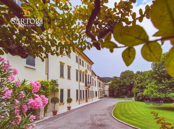 Outdoor view of the Sartori di Verona grounds, a semi-pan shot of the side of the building and front path, with the courtyard to the right.