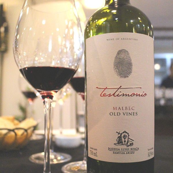 A tasting of Testimonio Old Vines Malbec sits in a wine glass to the right of a magnum sized bottle of the wine.