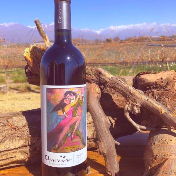 A bottle of Claroscuro Malbec by Bodega de Arte stands in front of old wooden logs, with the Claroscuro vineyards visible in the distance.