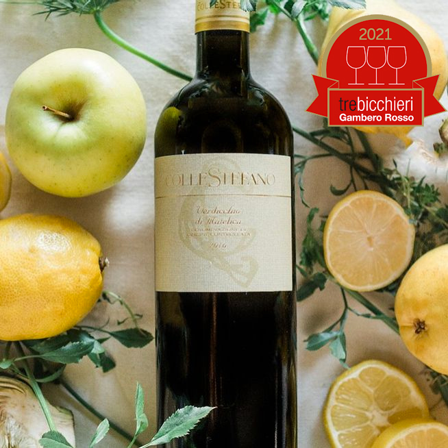 A bottle of ColleStefano Verdicchio di Matelica 2019 lays vertically on its side, label-up, with on-the-vine lemons, lemon slices and green apple surrounding it. The 2021 Tre Bicchieri Gambero Rosso stamp is on the upper right of the image.