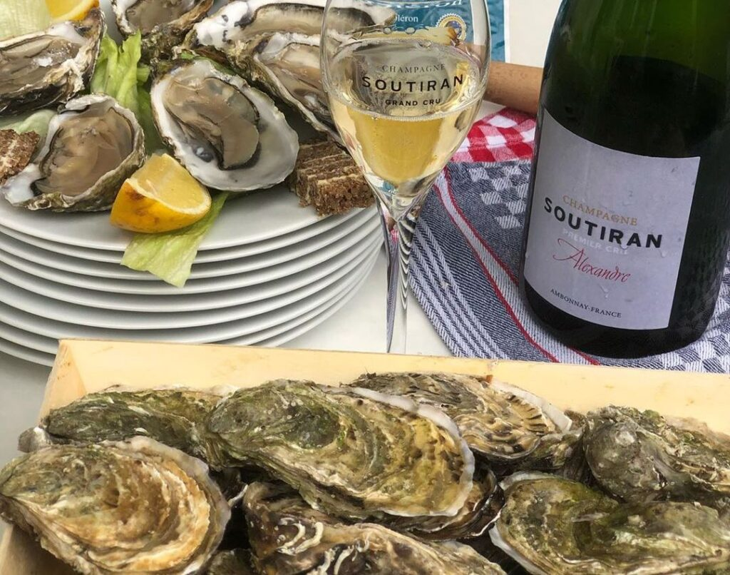 A bottle of Champagne Soutiran Premier Cru Alexandra sits off to the right, with a wine glass half full of it in the centre. In the foreground are a stack of fresh, unshucked oysters atop a wooden board. In the background, already shucked oysters sit atop a stack of white dinner plates with lettuce and lemon.