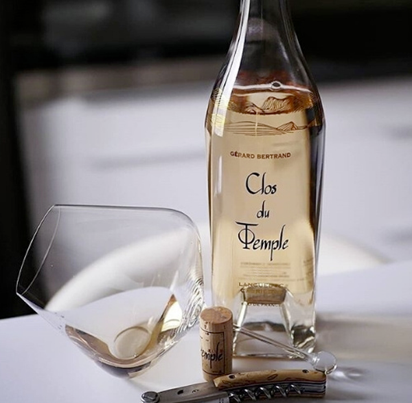 A bottle of Clos du Temple sits on a white table in the foreground, a tasting of it sits in a spillproof wine glass perched on itself directly in front of the bottle. The cork and corkscrew artfully arranged in front of the wine glass and wine bottle.