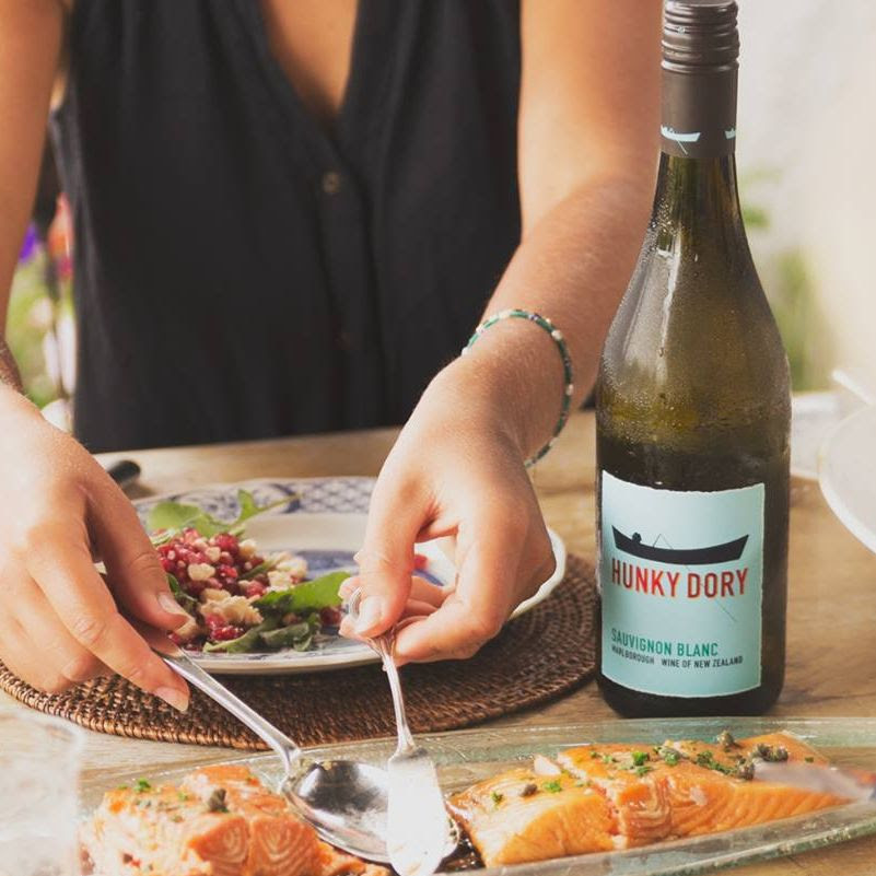 An image of a fair-skinned woman wearing a navy button-up tank top, sat at a light-coloured wooden table. A white and blue porcelain sits atop a wicker placement in front of her, with cranberry arugula salad sat to one side, as she helps herself to grilled pistachio salmon from a serving platter. A chilled bottle of Hunky Dory Sauvignon Blanc sits to the right of her and her plate, just behind the platter of salmon.
