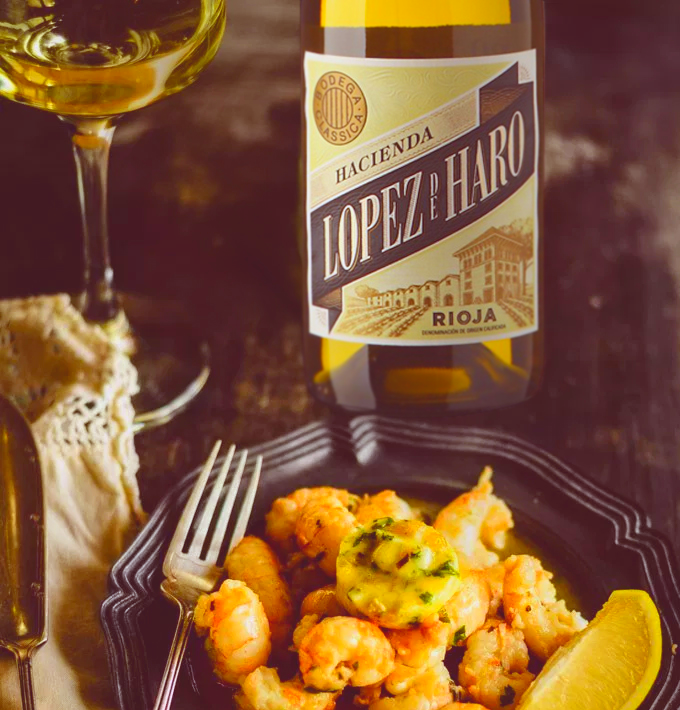 In the foreground, an Old-Spanish style navy dinner plate holds cooked lemon shrimp, a fork perched on the left lip of the plate. Behind the plate is a glass and bottle of Hacienda Lopez de Haro Rioja Blanco. All items are atop an old dark wooden table.