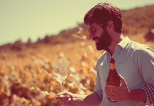 Bodega Hacienda Lopez de Haro founder Richi Ambarri walks through the vineyard holding an open bottle of Rioja Blanco, and a wine glass to enjoy it in in the other hand.